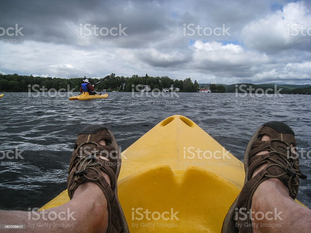 People kayaking on a lake from personal point of view stock photo