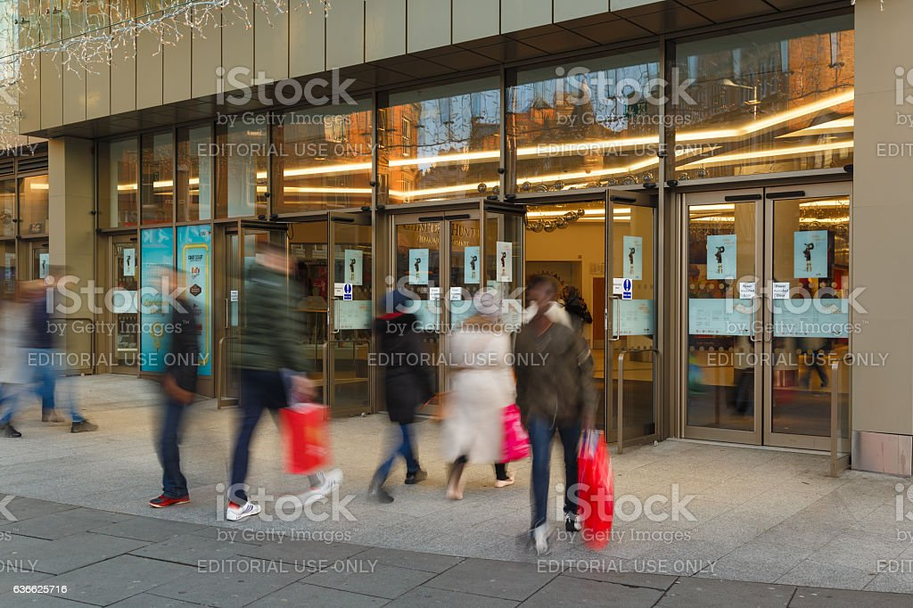 People leave shopping mall with bags on Boxing Day sales stock photo