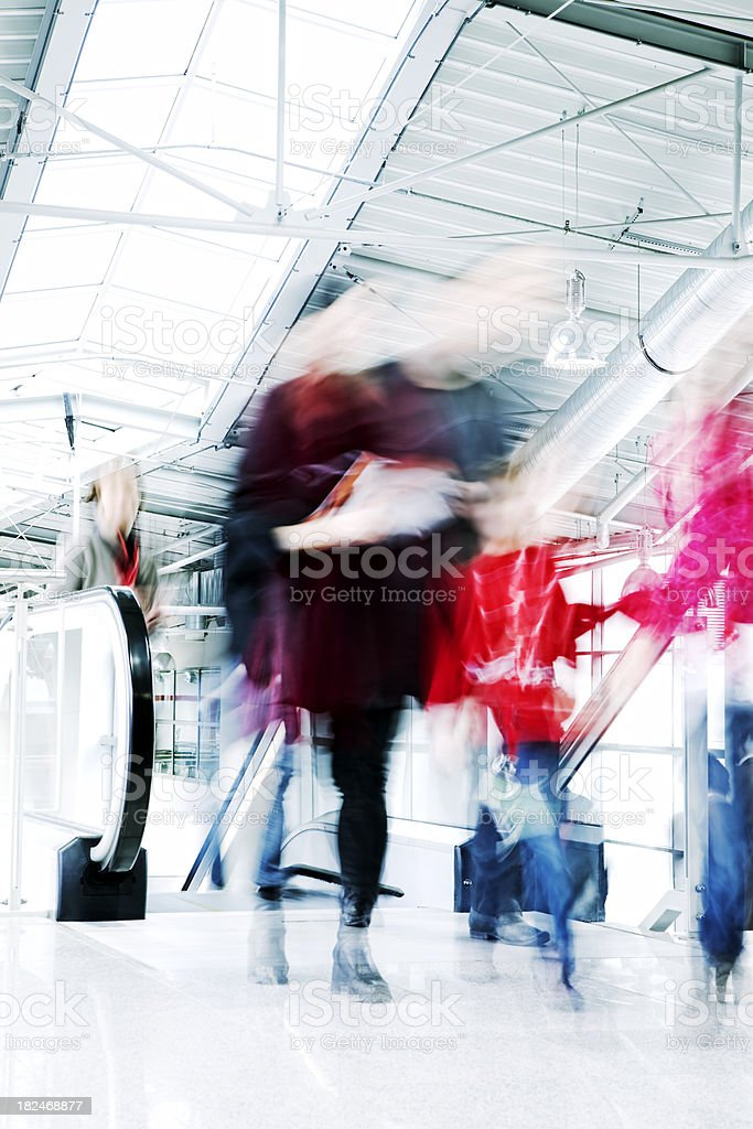 People Leaving Escalator in a Modern Interior, Blurred Motion royalty-free stock photo