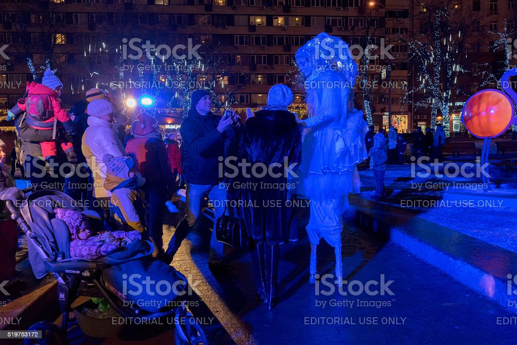 People look at actors on stilts in night street performance stock photo
