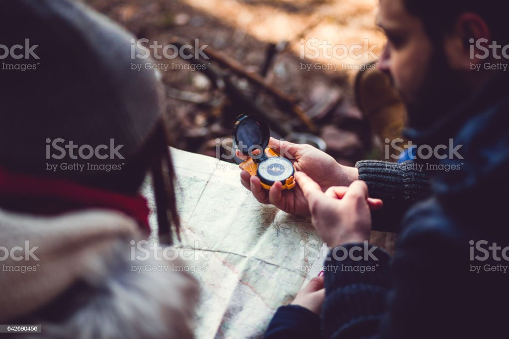 People Looking At Compas On Camping In Woods stock photo
