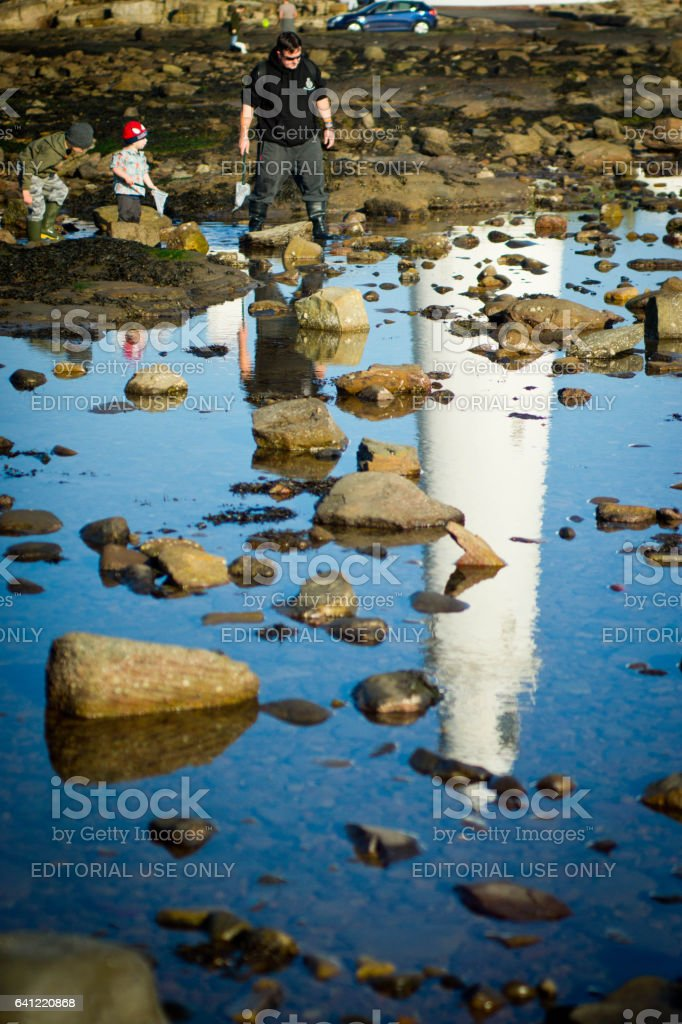 People looking into a rock pool stock photo