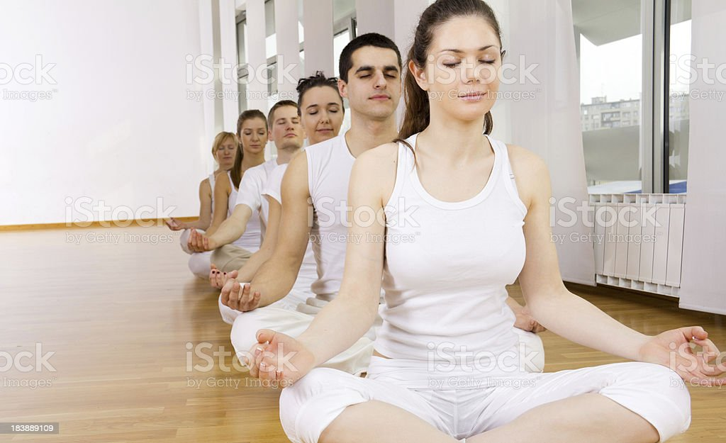 People meditating, lotus pose, sitting in a row. royalty-free stock photo