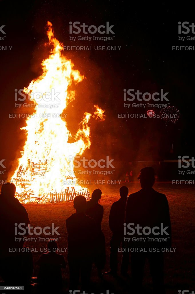 People meeting around big bonfire with fireworks in background stock photo