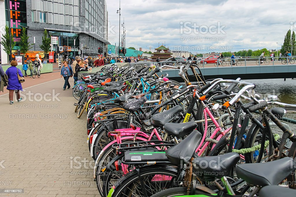 People near the bicycle parking on  waterfront canal in Amsterdam stock photo