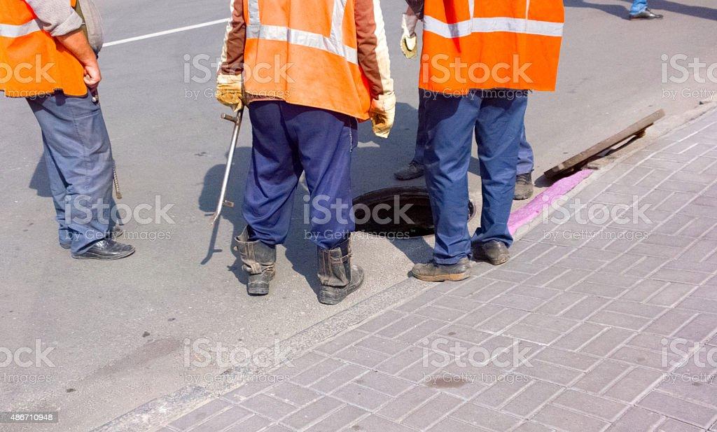 People near the manhole. stock photo