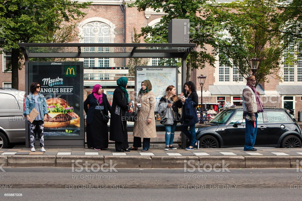 People of different ethnic groups are waiting in a public transport station stock photo