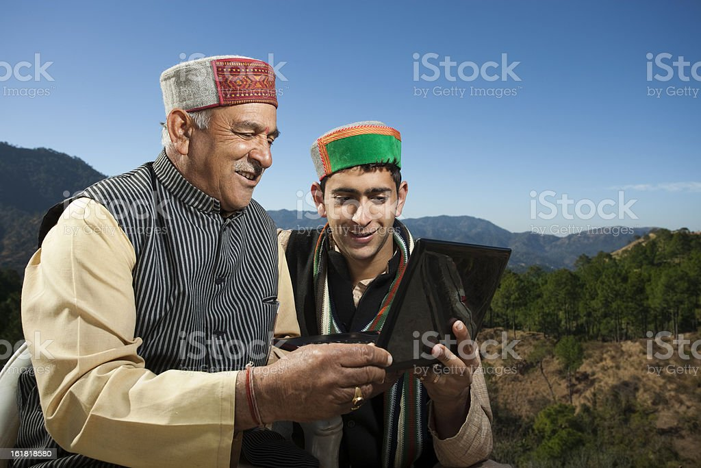 People of Himachal Pradesh: Grandson showing laptop to grandfather royalty-free stock photo