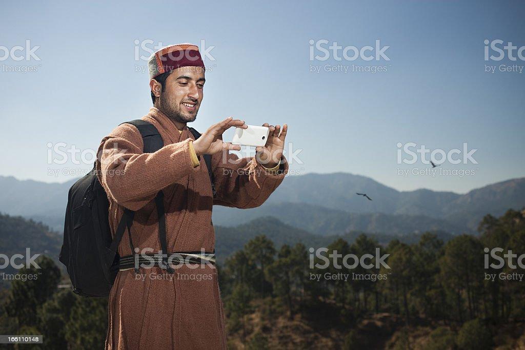 People of Himachal Pradesh: Traveler taking photos through phone royalty-free stock photo