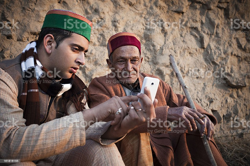 People of Himachal Pradesh: Young man showing phone to grandfather stock photo