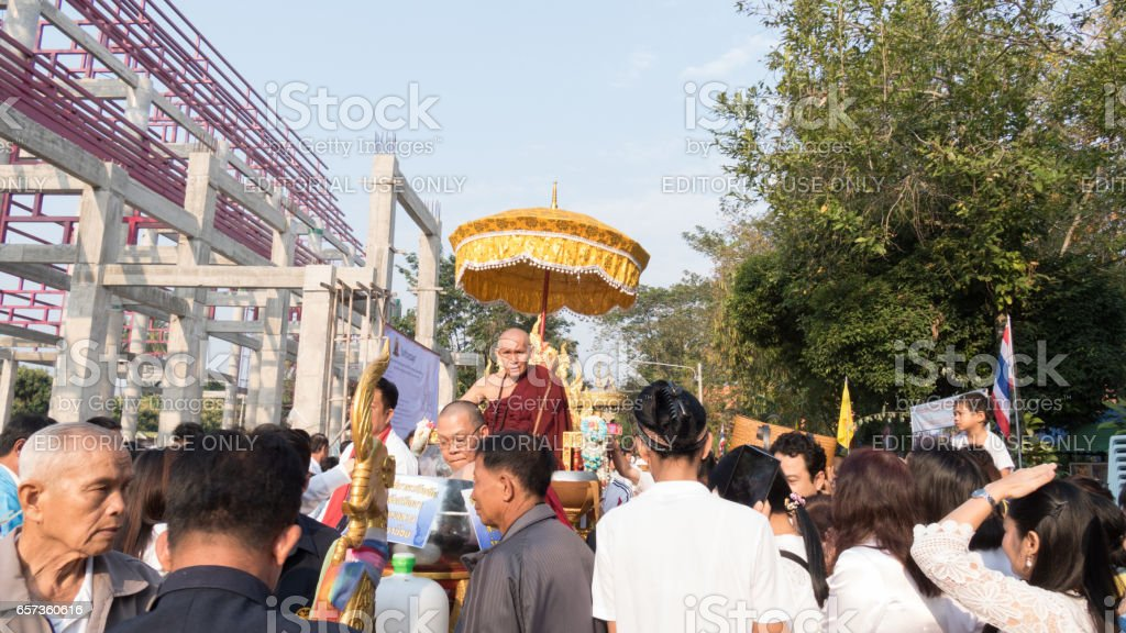people offering food and items to a buddhist monk stock photo