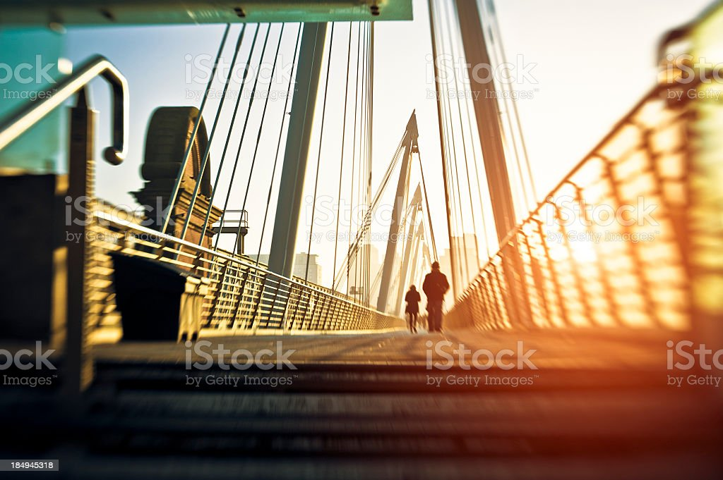 People On A Contemporary Bridge In London At Dawn stock photo