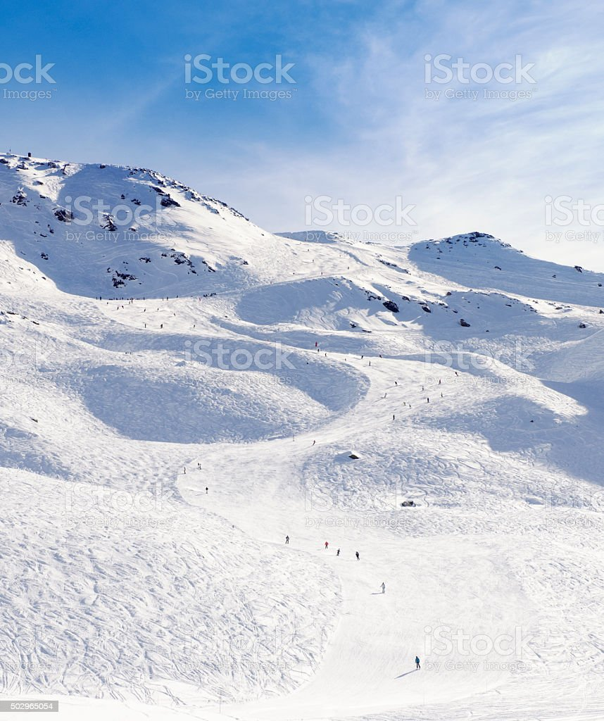 People on a Curving ski piste in the French Alps stock photo