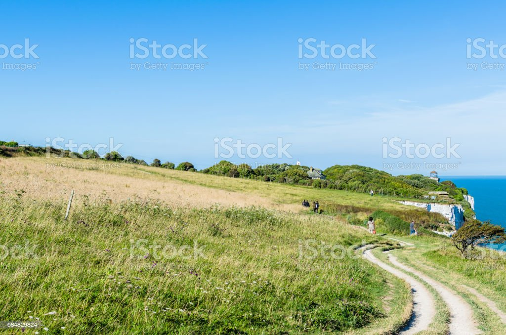 People on a winding footpath by a green field by White Cliffs stock photo