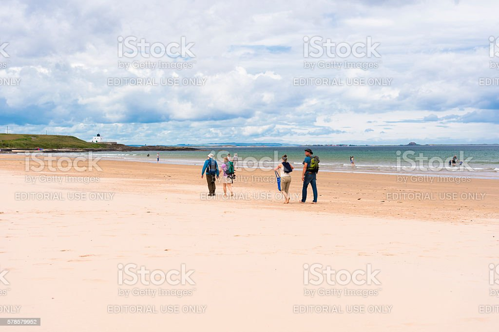 People on Bamburgh beach in Northumberland, north east England stock photo
