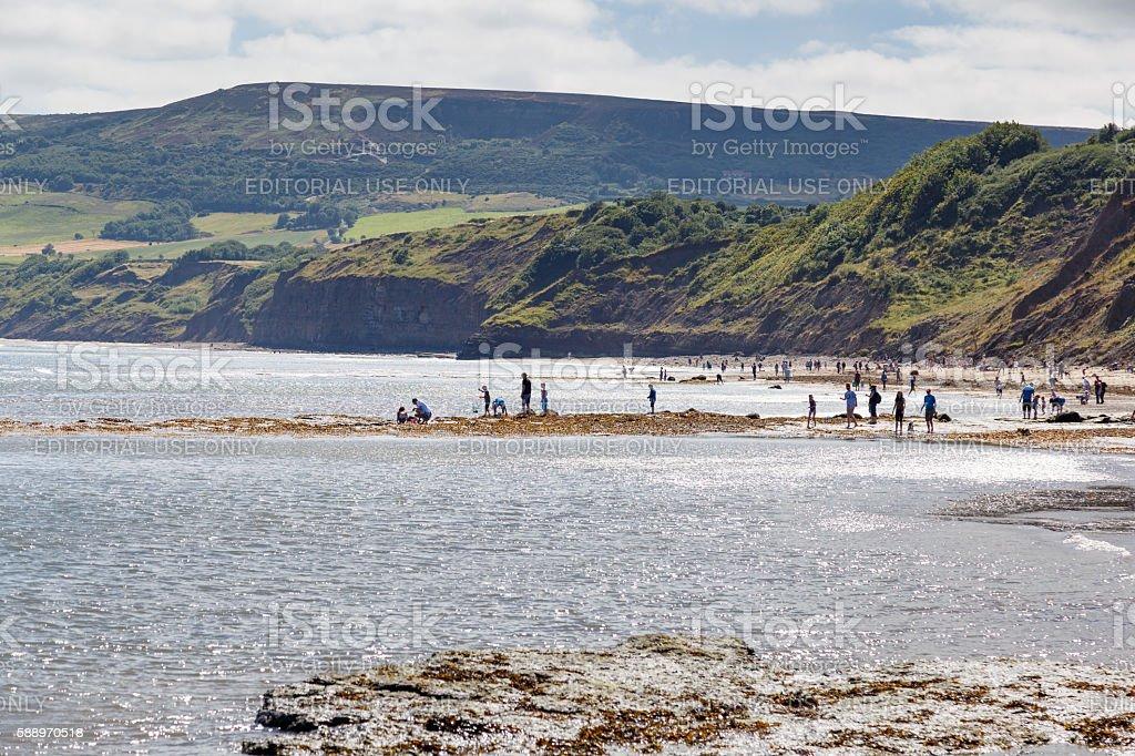 people on beach, fishing and crabbing, Robin Hoods Bay stock photo
