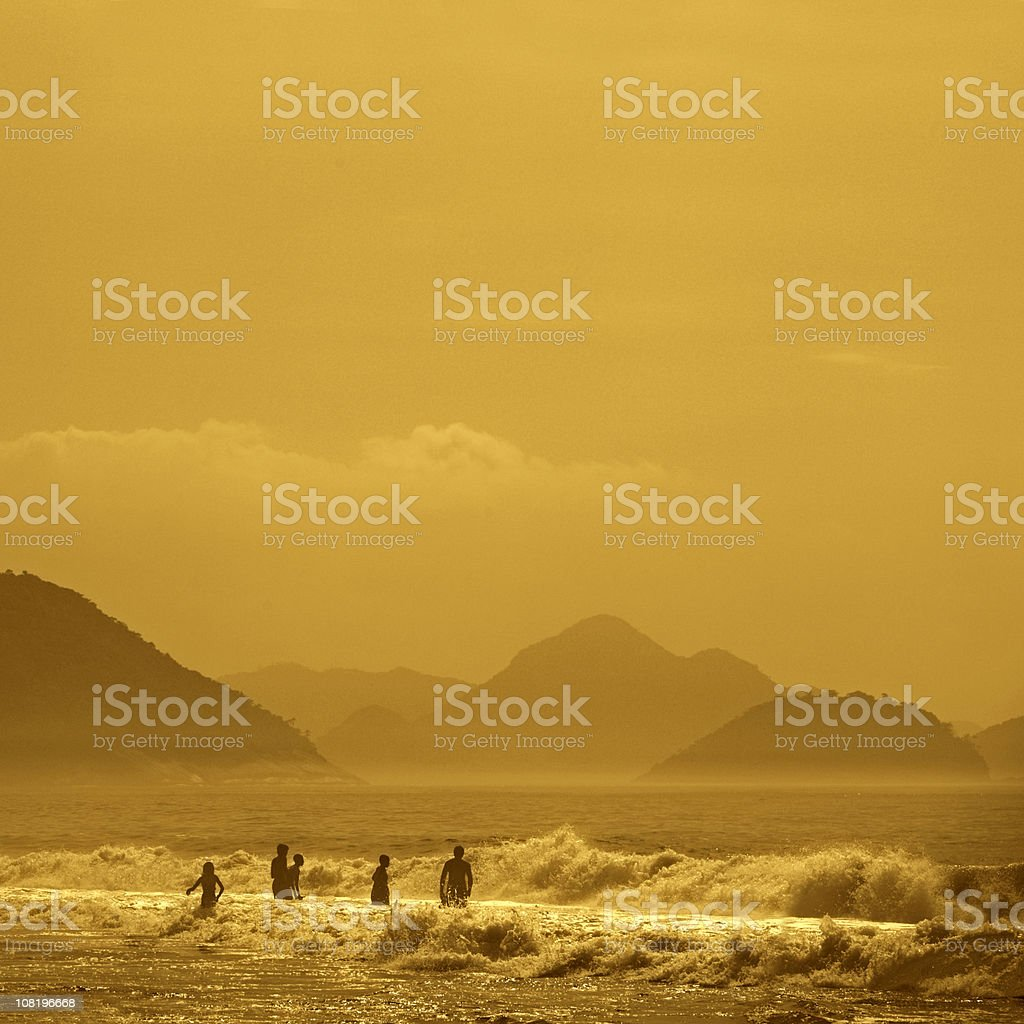 People on Beach with Mountains in Background royalty-free stock photo