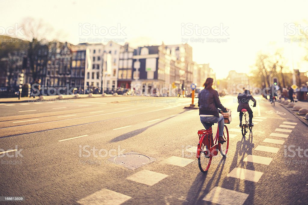 People on bikes in Amsterdam streets at sunset stock photo