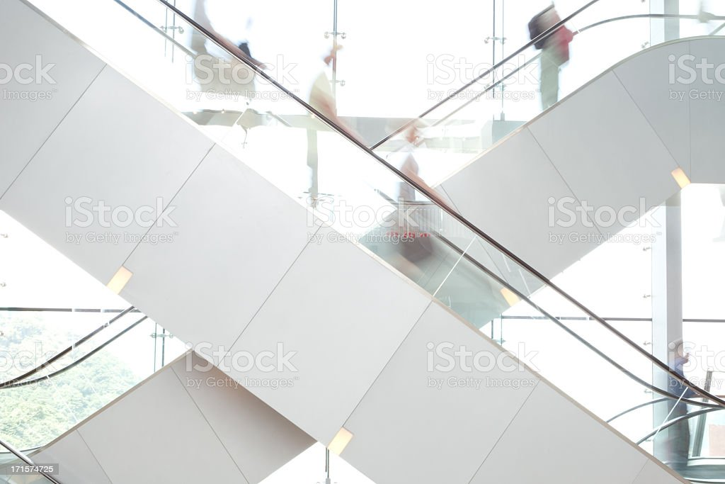 People on escalators in bright room stock photo