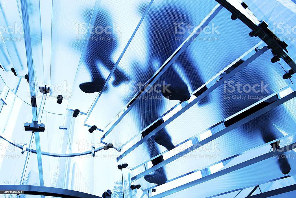 people on glass staircase stock photo