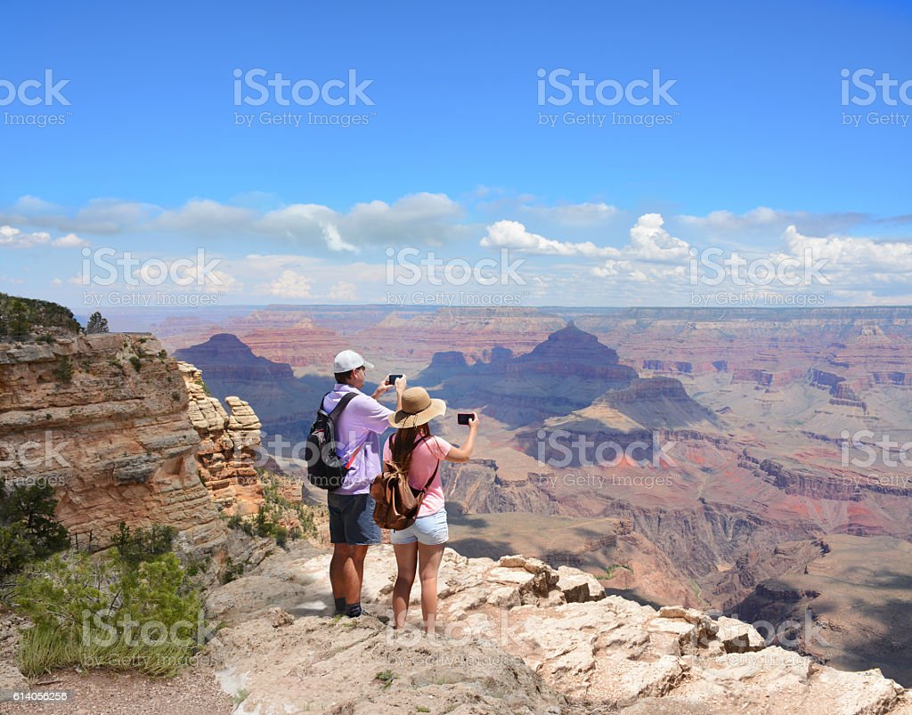 People on hiking trip taking pictures of beautiful landscape. stock photo