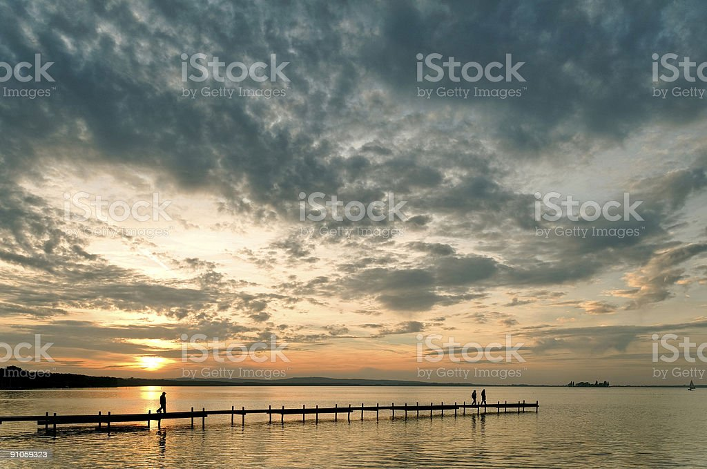 People on lakeside jetty with majestic cloudscape at sunset royalty-free stock photo