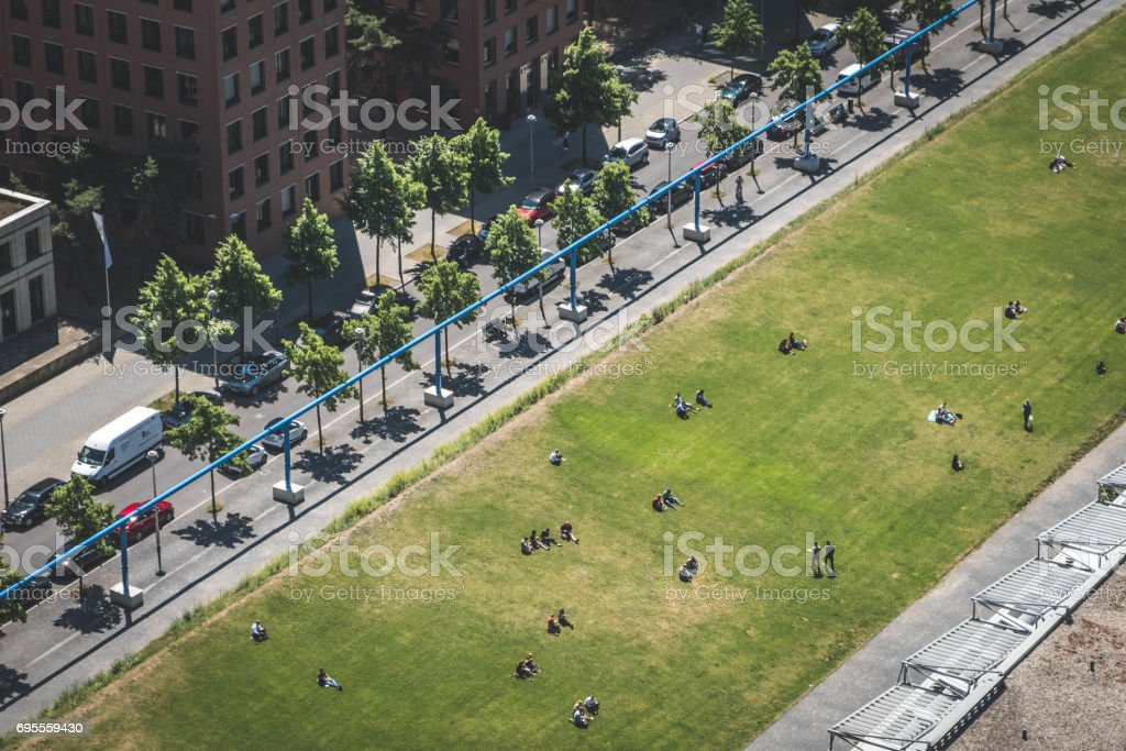 people on meadow in public park - cityscape aerial stock photo