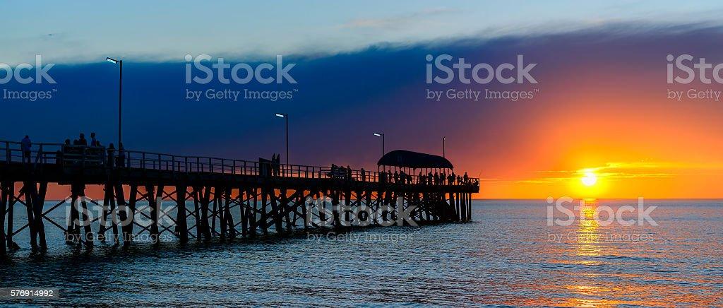 People on pier at sunset stock photo