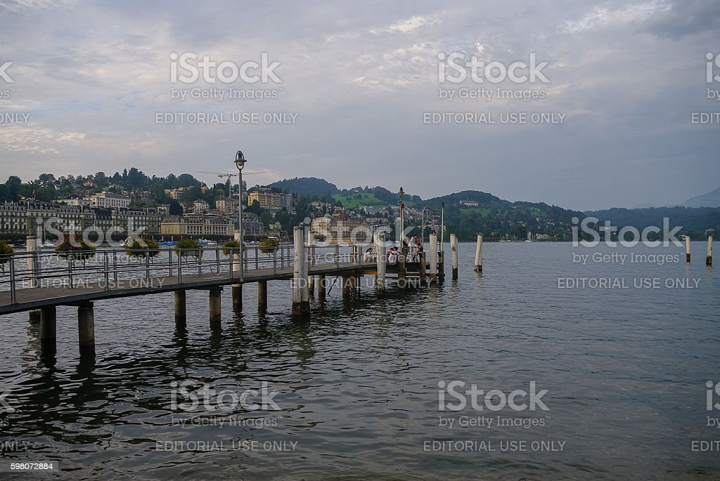 People on pier with lake and old town at background. stock photo