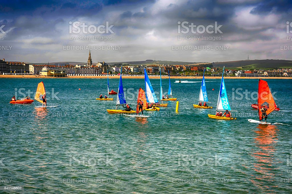 People on sailboards and in sailboats in Weymouth bay, UK stock photo