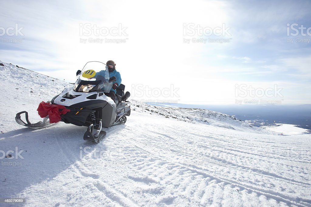 people on snowmobile in winter mountain stock photo