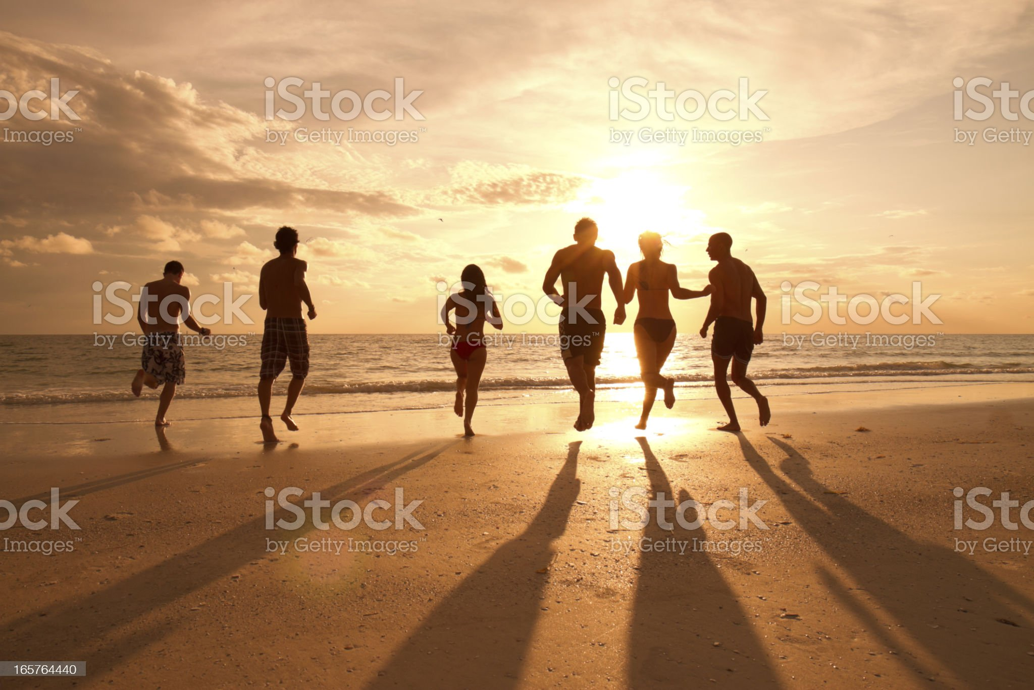 People on the beach running to the water at sunset royalty-free stock photo