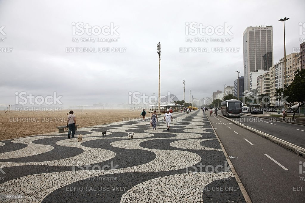 People on the seafront walkway at Copacabana beach royalty-free stock photo