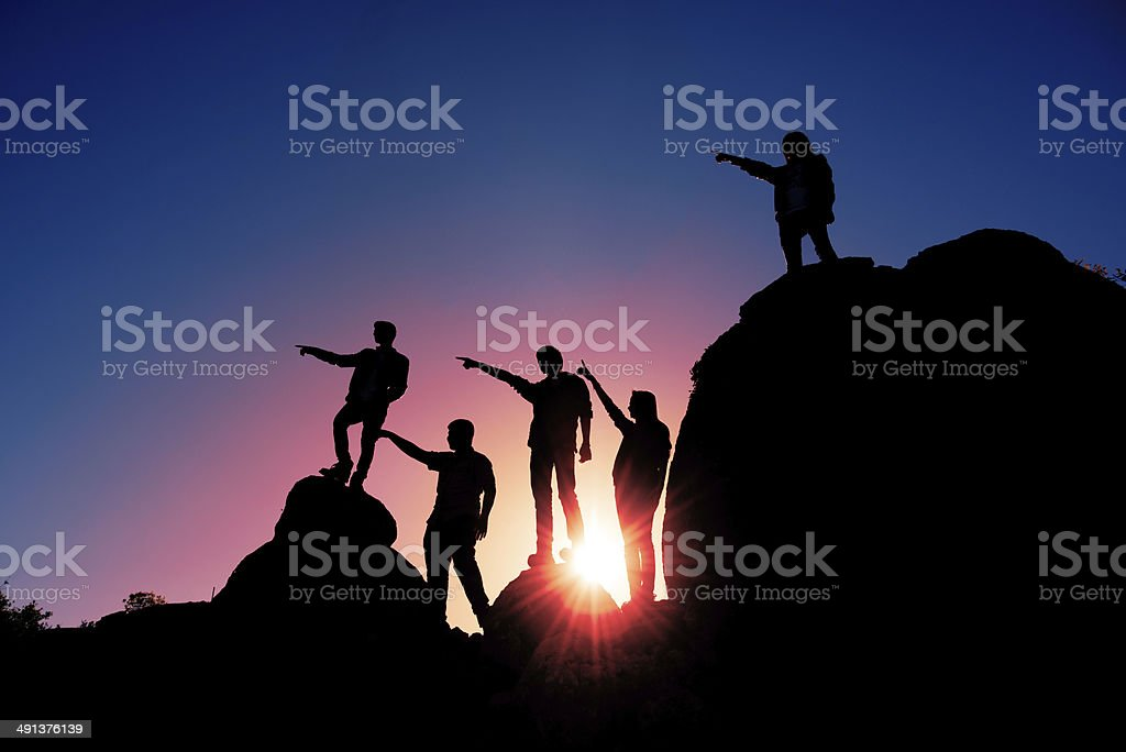 People on top of rocky mountains stock photo