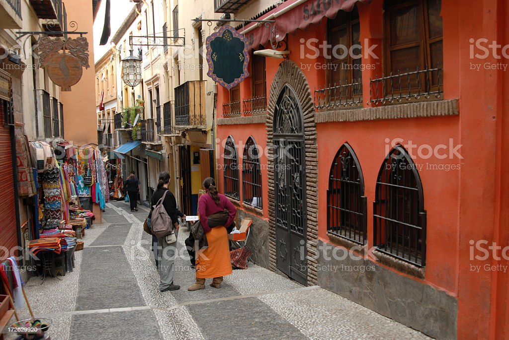 People on walkway between buildings in Albaycin, Granada stock photo
