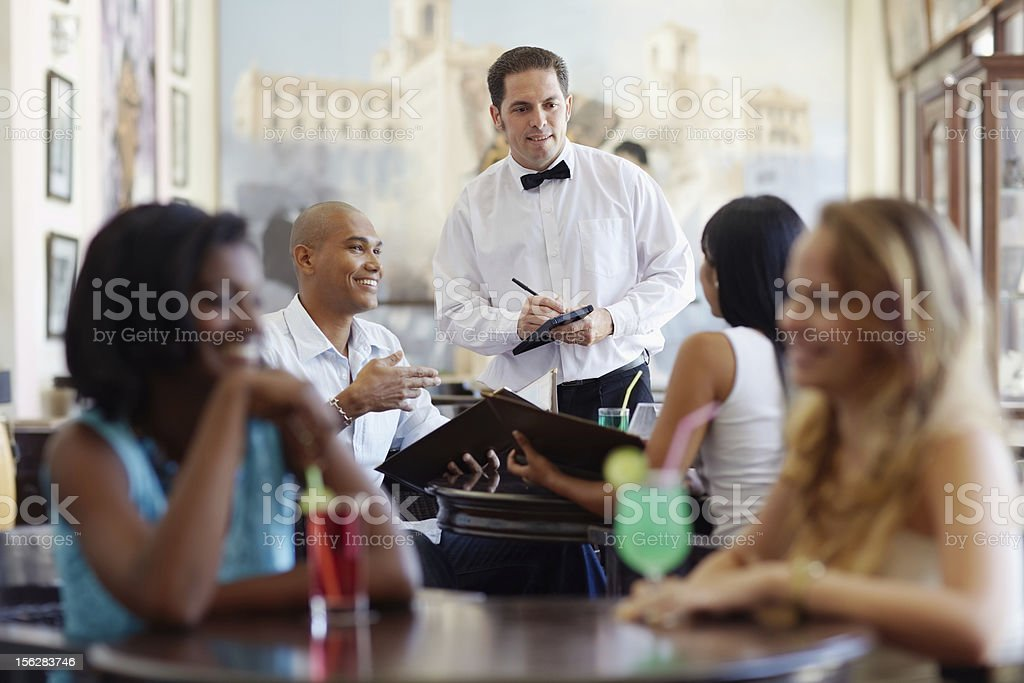 people ordering meal to waiter in restaurant stock photo