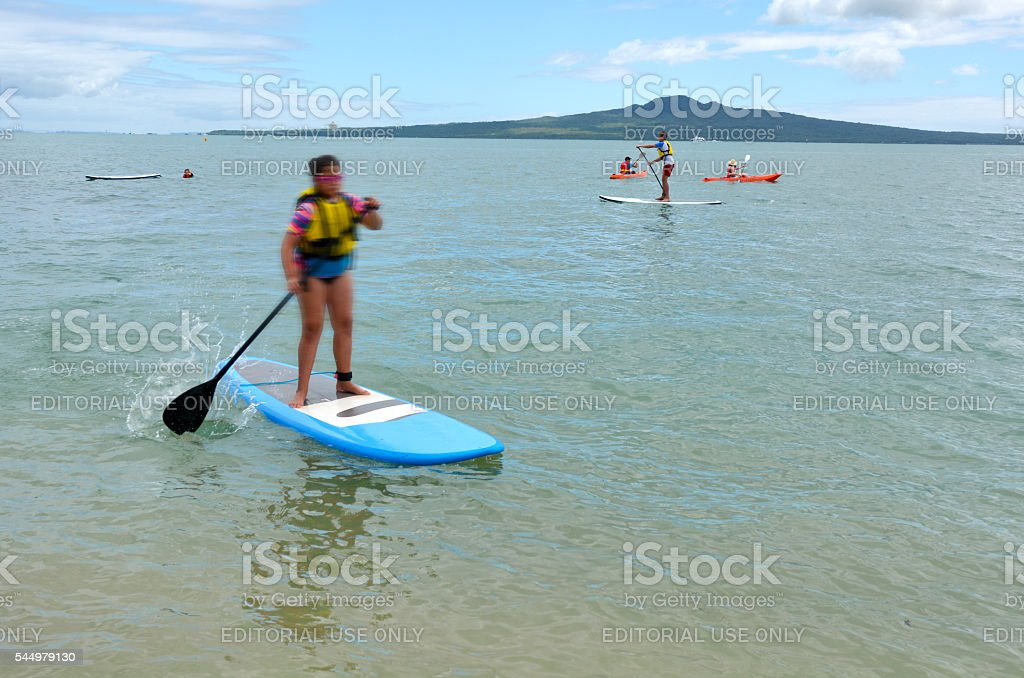 People paddle boarding in mission bay in Auckland New Zealand stock photo