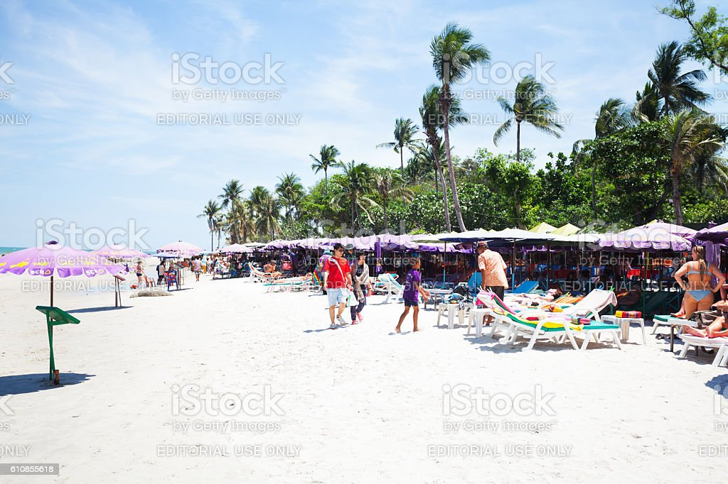 People, parasols and sun loungers on beach stock photo