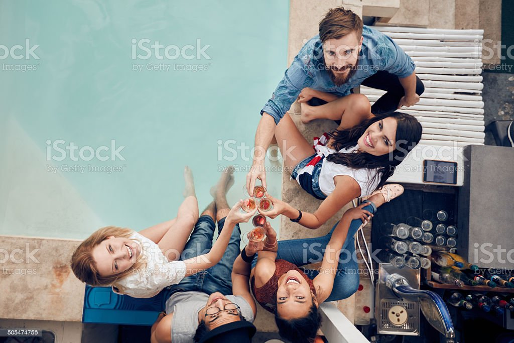 People partying by the pool toasting wine stock photo