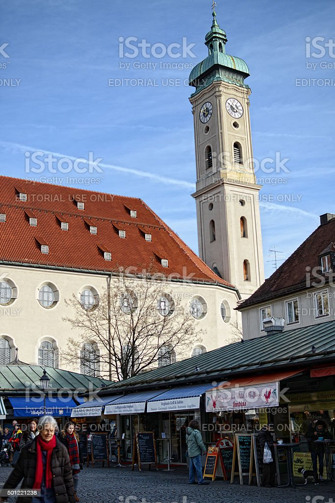 people passing by Heiliggeistkirche (Munich) at Viktualienmarkt stock photo