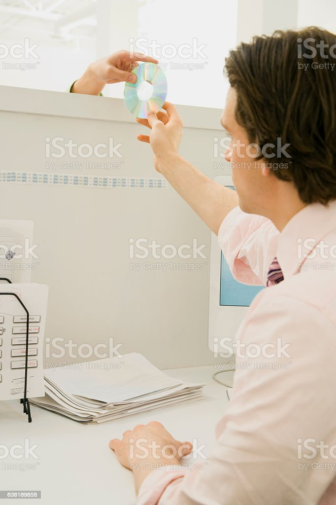 People passing DVD media disk over office cubicle wall stock photo