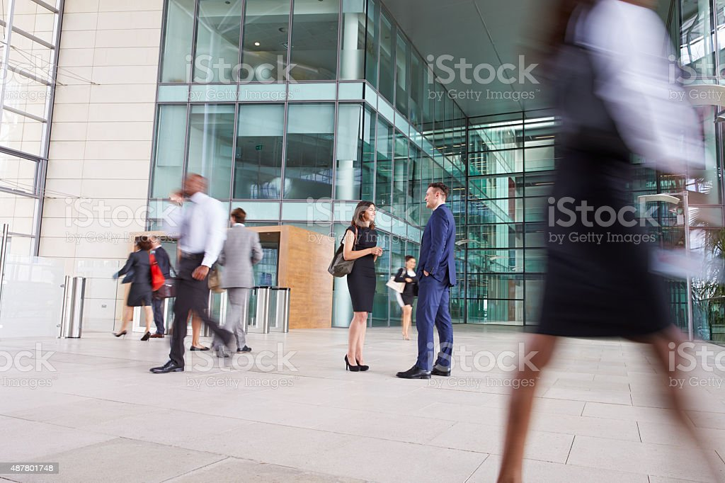 People passing through the busy foyer of a business building stock photo