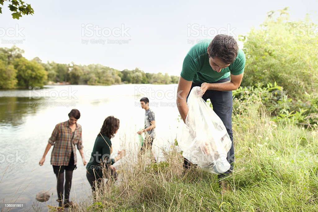 People picking up garbage in park stock photo