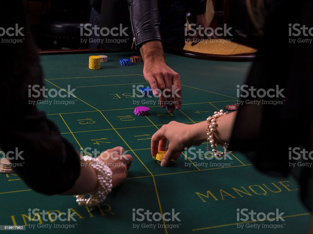 People placing gambling chips for bets at the casino stock photo