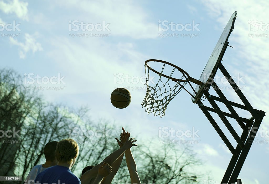 People playing basketball outdoors stock photo