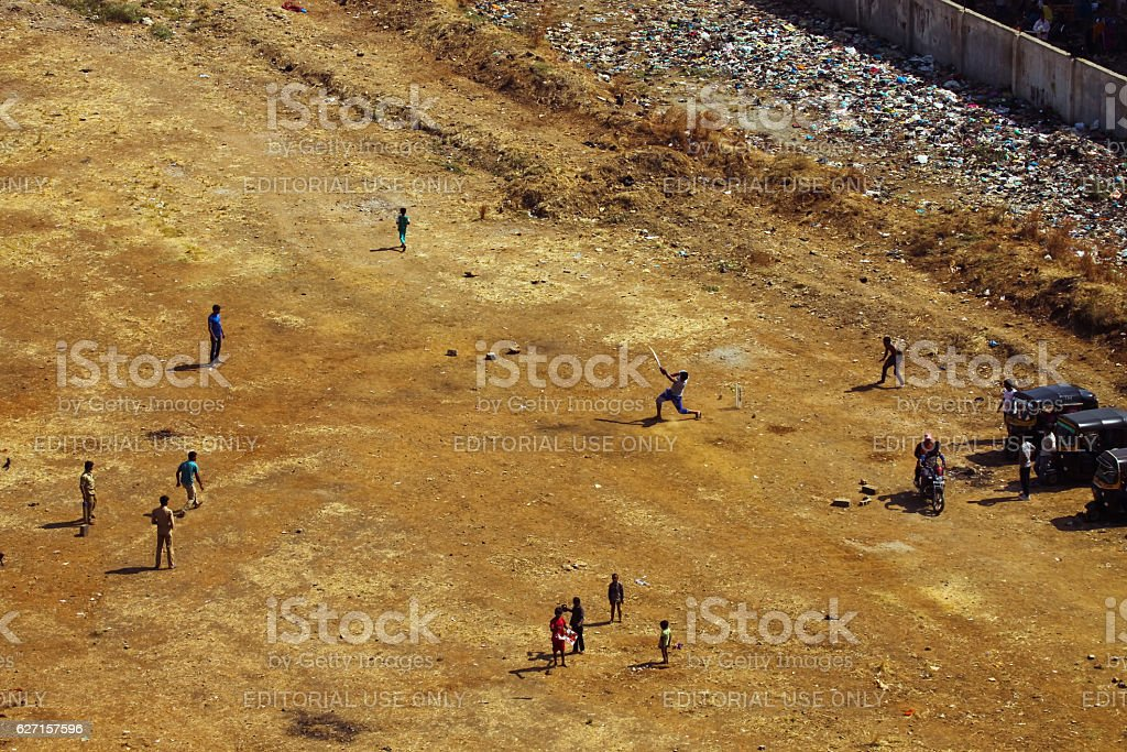 People playing cricket and children flying kite stock photo