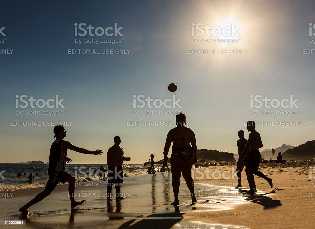 People Playing Football in a Beach stock photo