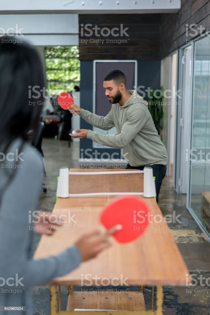 People playing ping-pong at the office stock photo
