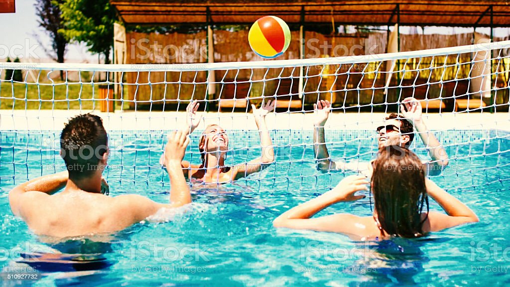 People playing volleybay in swimming pool and having beers. stock photo