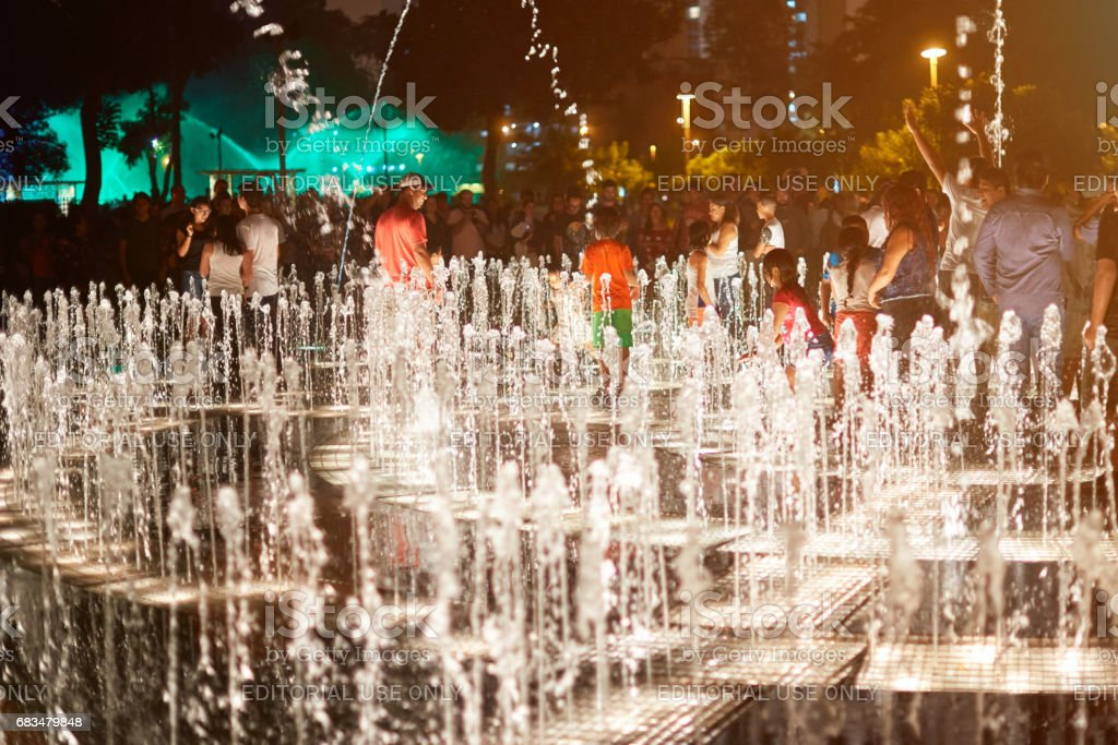 People playing with music fountain stock photo